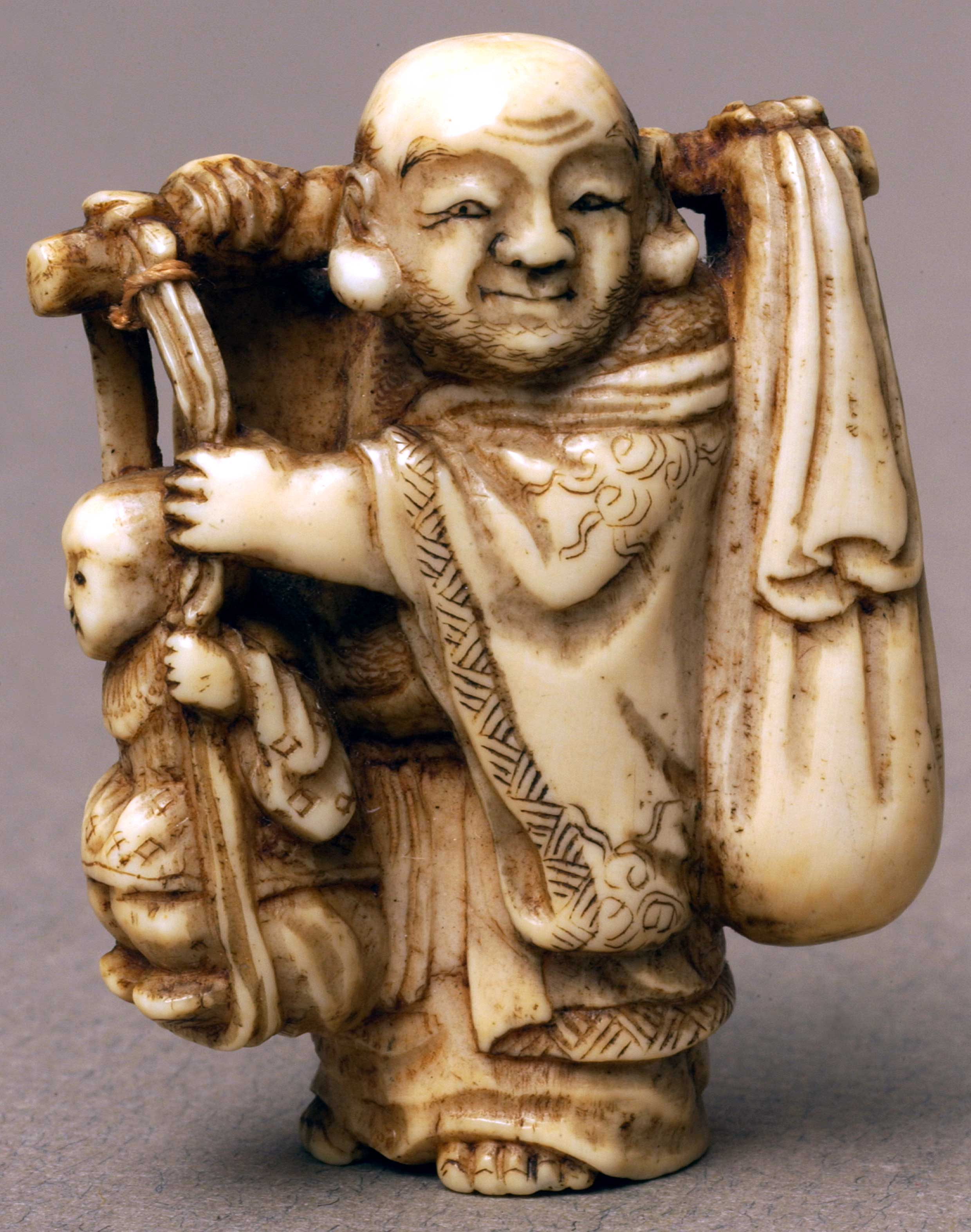 Netsuke depicting a man carrying a branch