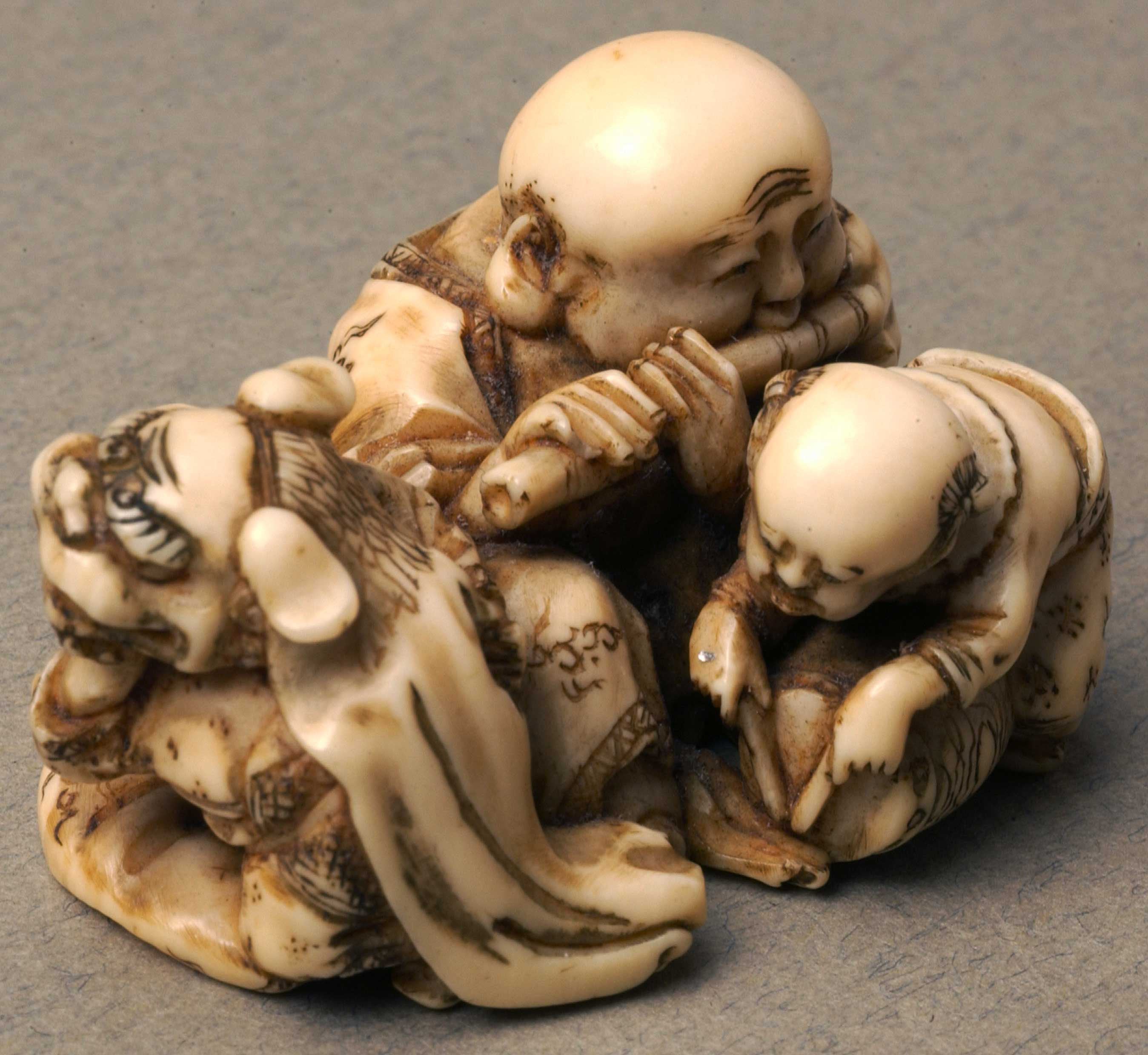 Netsuke depicting three men