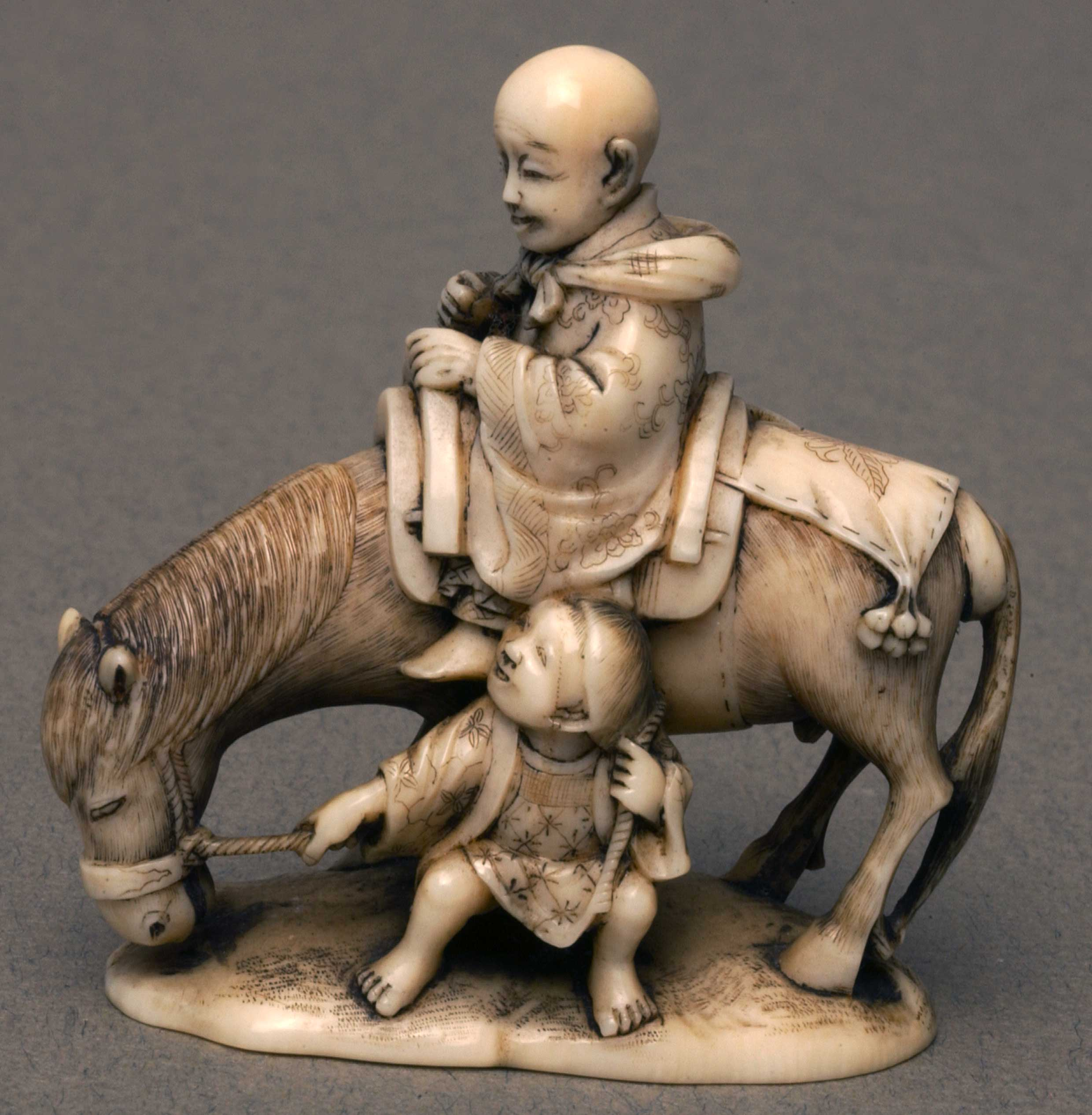 Netsuke depicting a man seated on a donkey