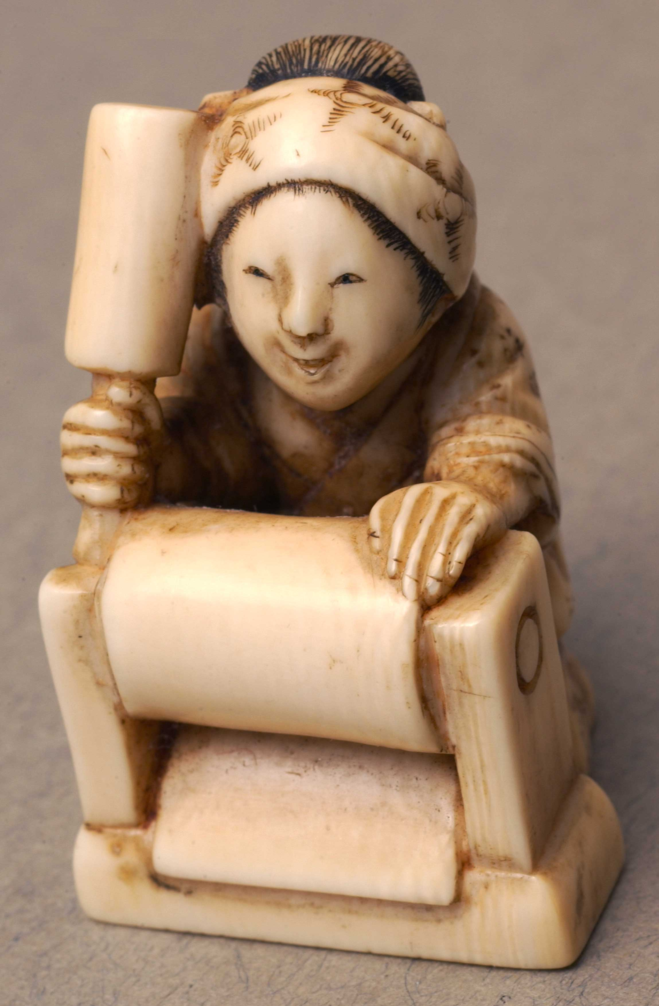 Netsuke depicting a woman in traditional Japanese clothing